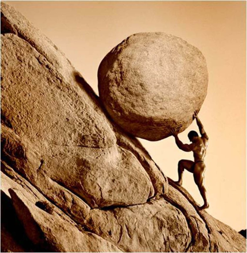 Man pushing his dream forward represented as a boulder being pushed up a rock face.